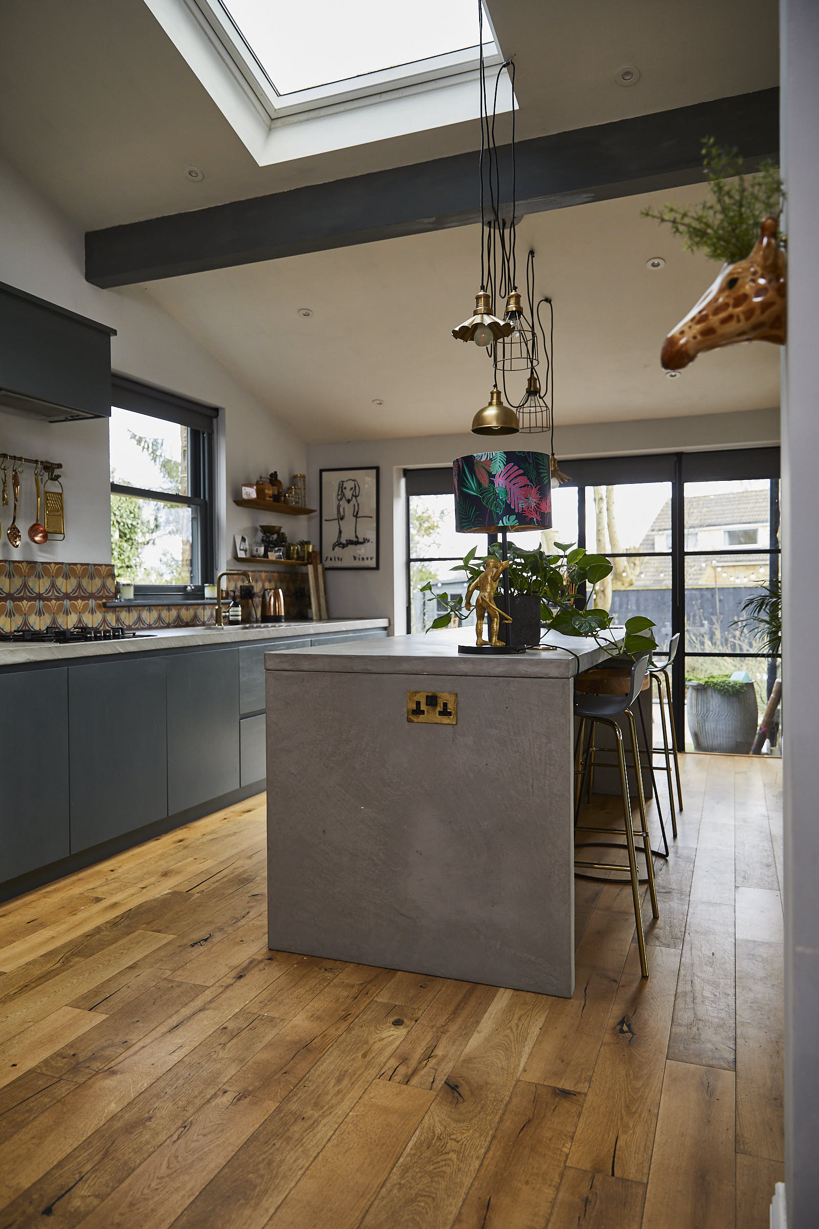 Solid concrete grey kitchen island with pendant lights above with geometric metal shades