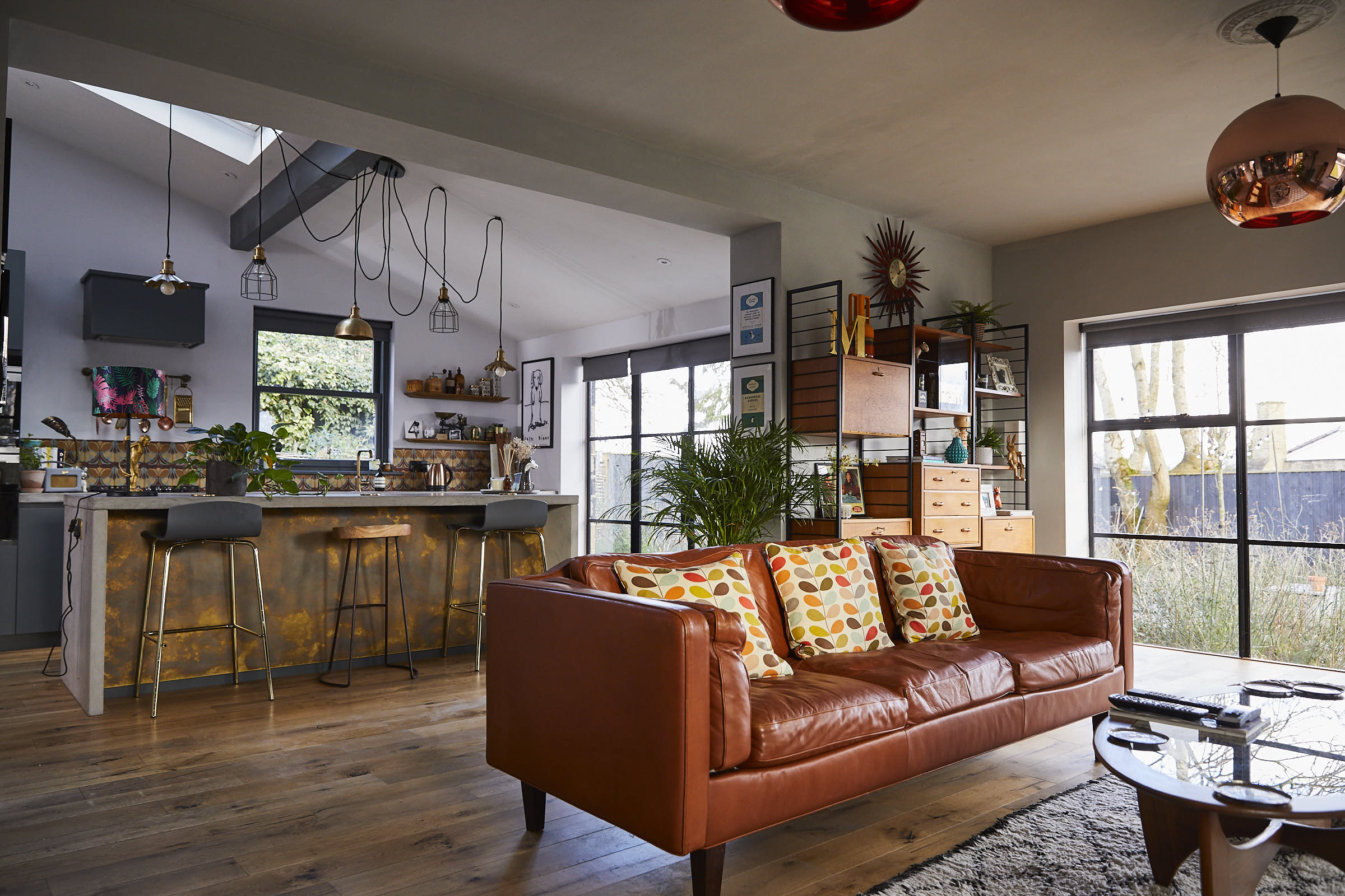 Brown leather sofa with yellow cushions in open plan kitchen and dining room