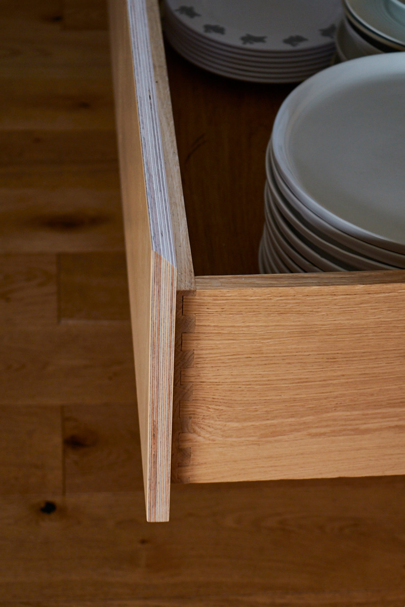 Solid oak drawer box with stack of ceramic plates
