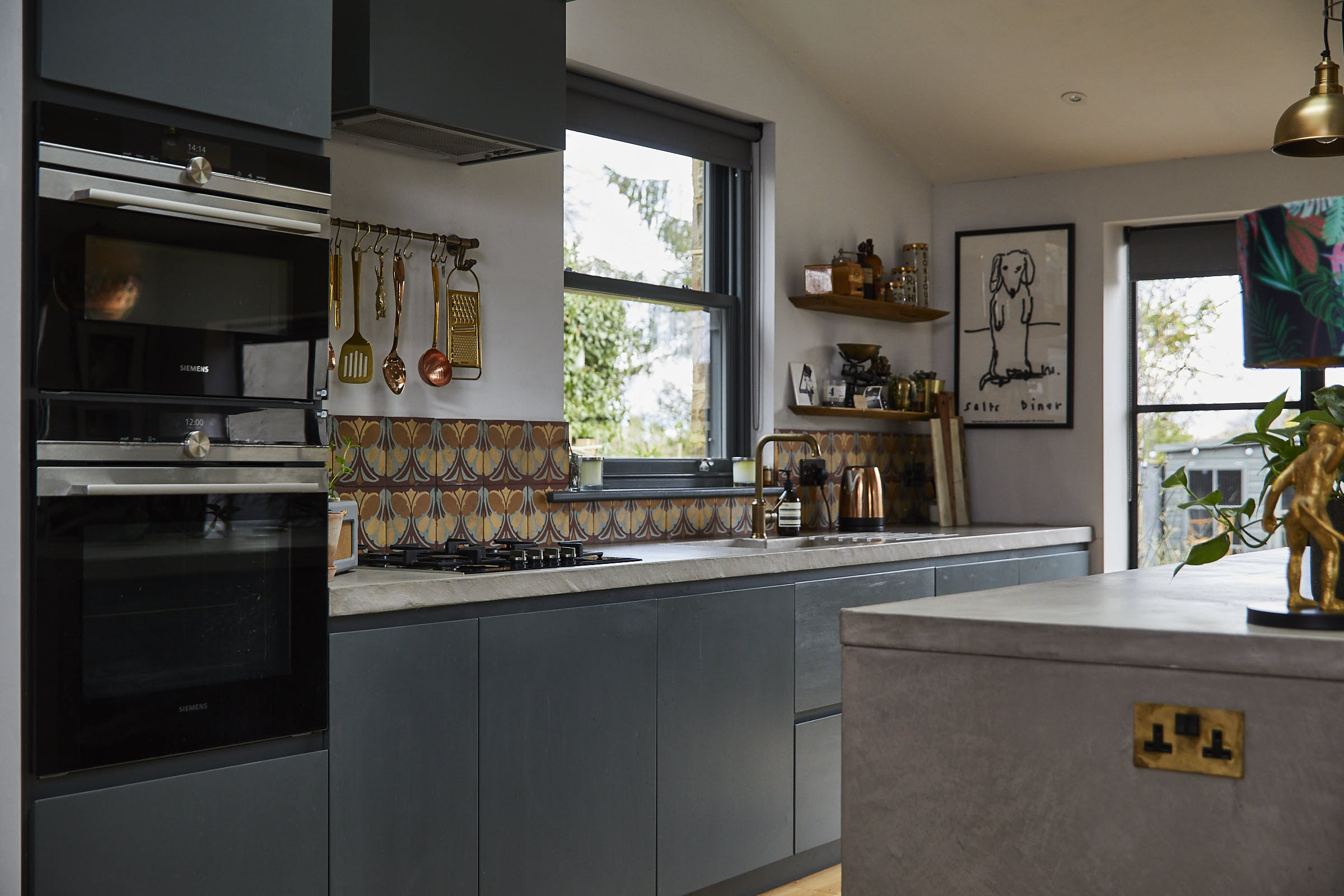 Bespoke painted kitchen with solid concrete worktops and colourful shell tiles