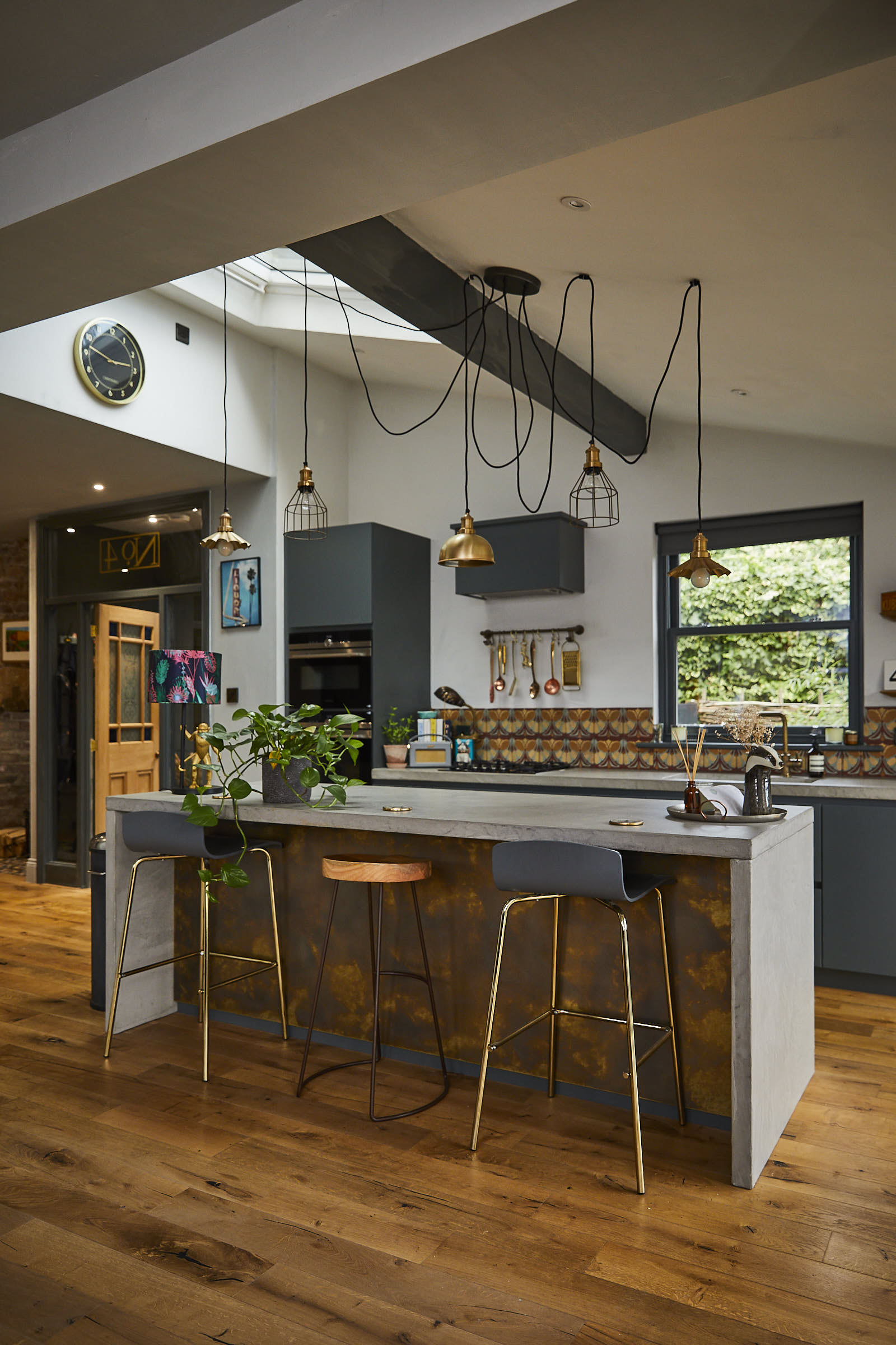 Bar stools sit under kitchen island with concrete waterfall worktop and clean oak flooring
