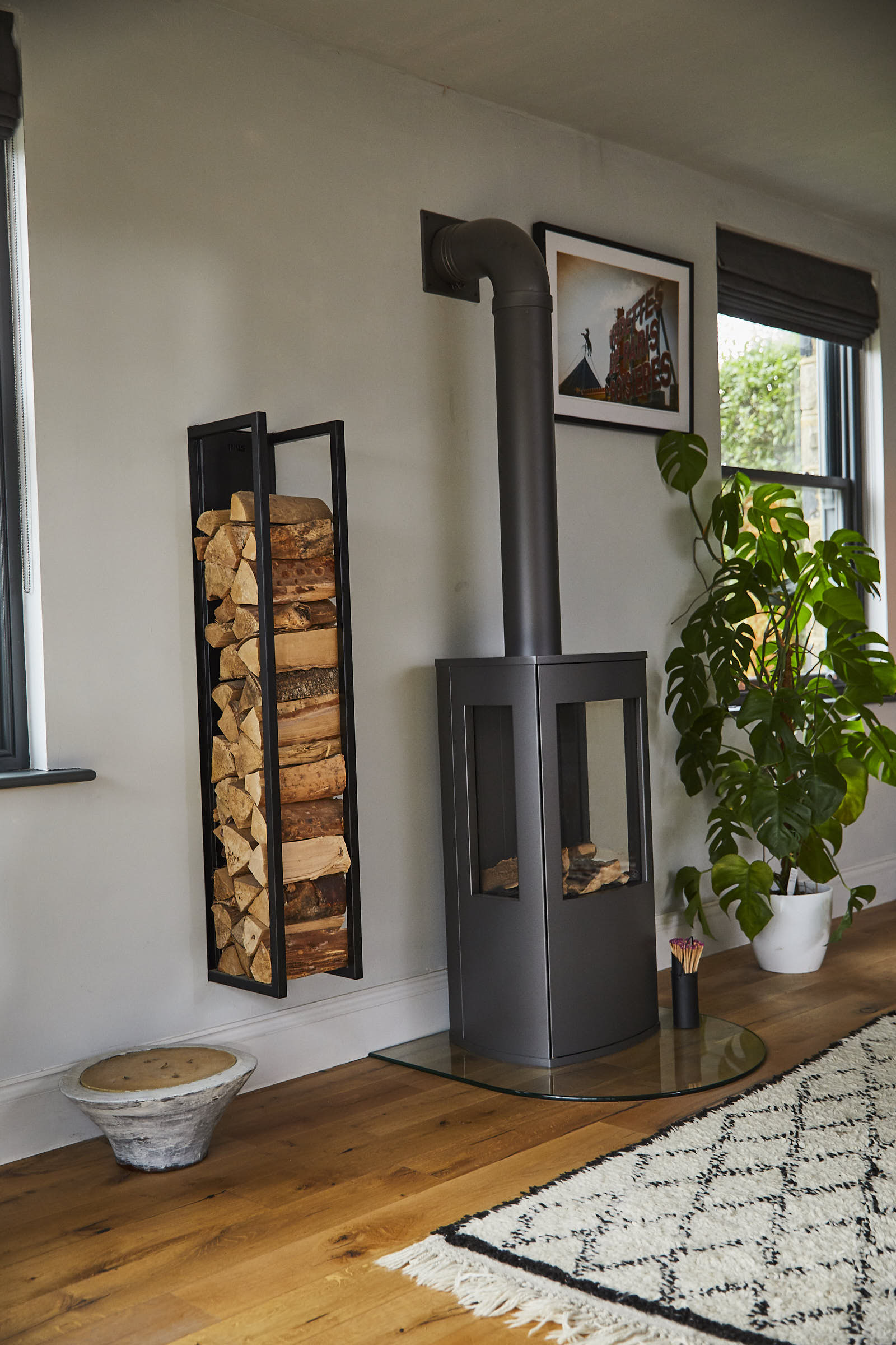 Black log burner with open log storage attached against wall