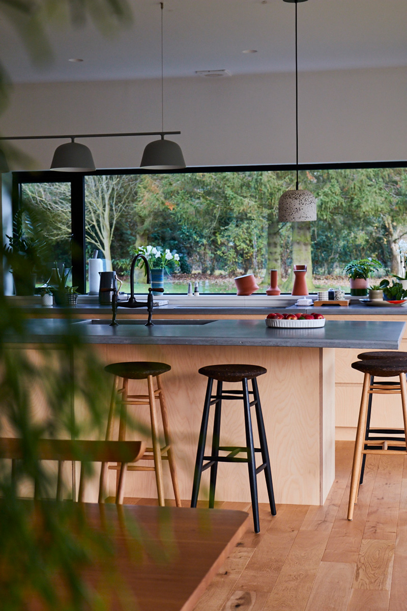 Stools sit under concrete breakfast bar in light birch wood kitchen