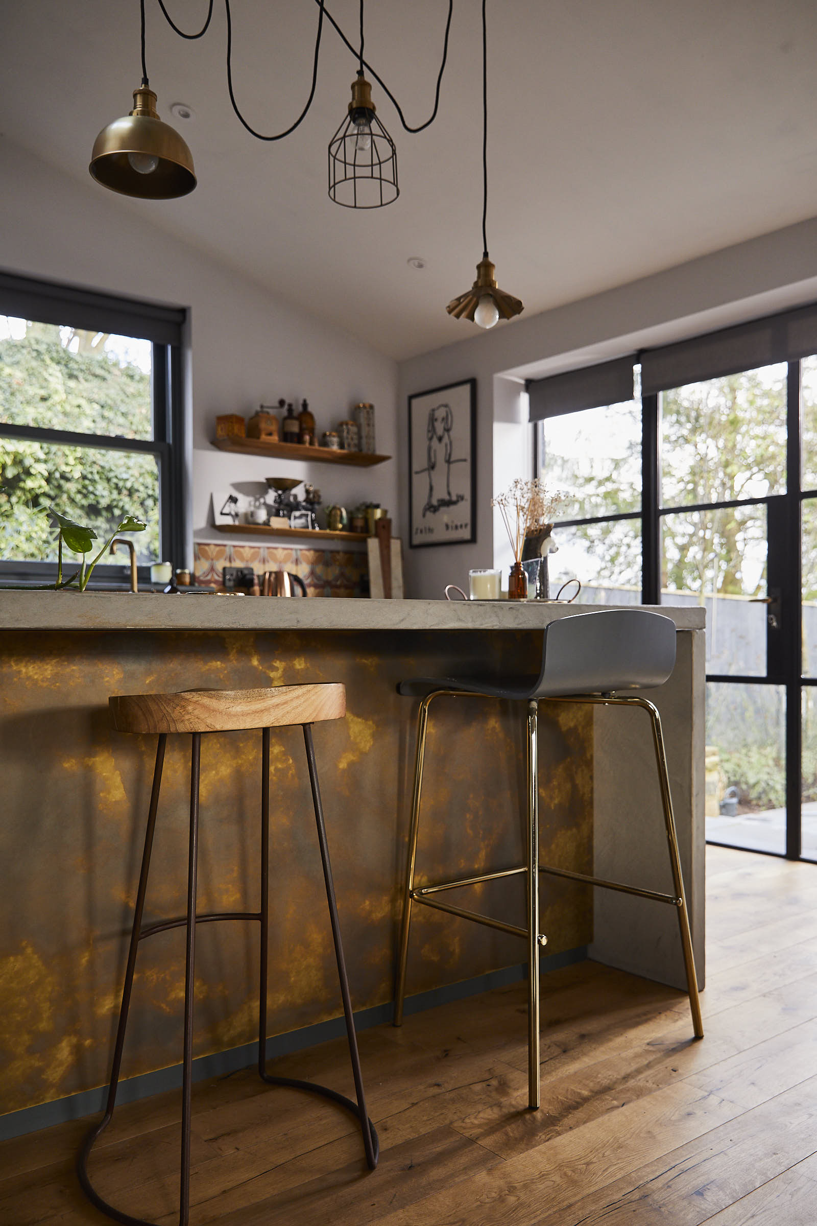 Oak and metal bar stool under solid grey concrete breakfast bar with antique brass back panel