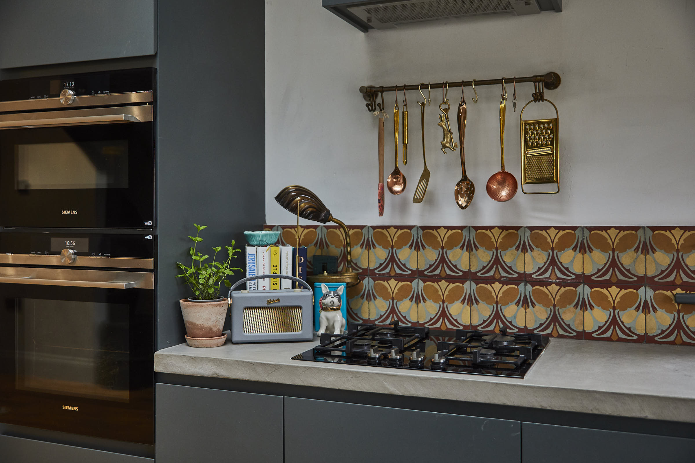 Copper utensils hand over gas hob with colourful shell tiles