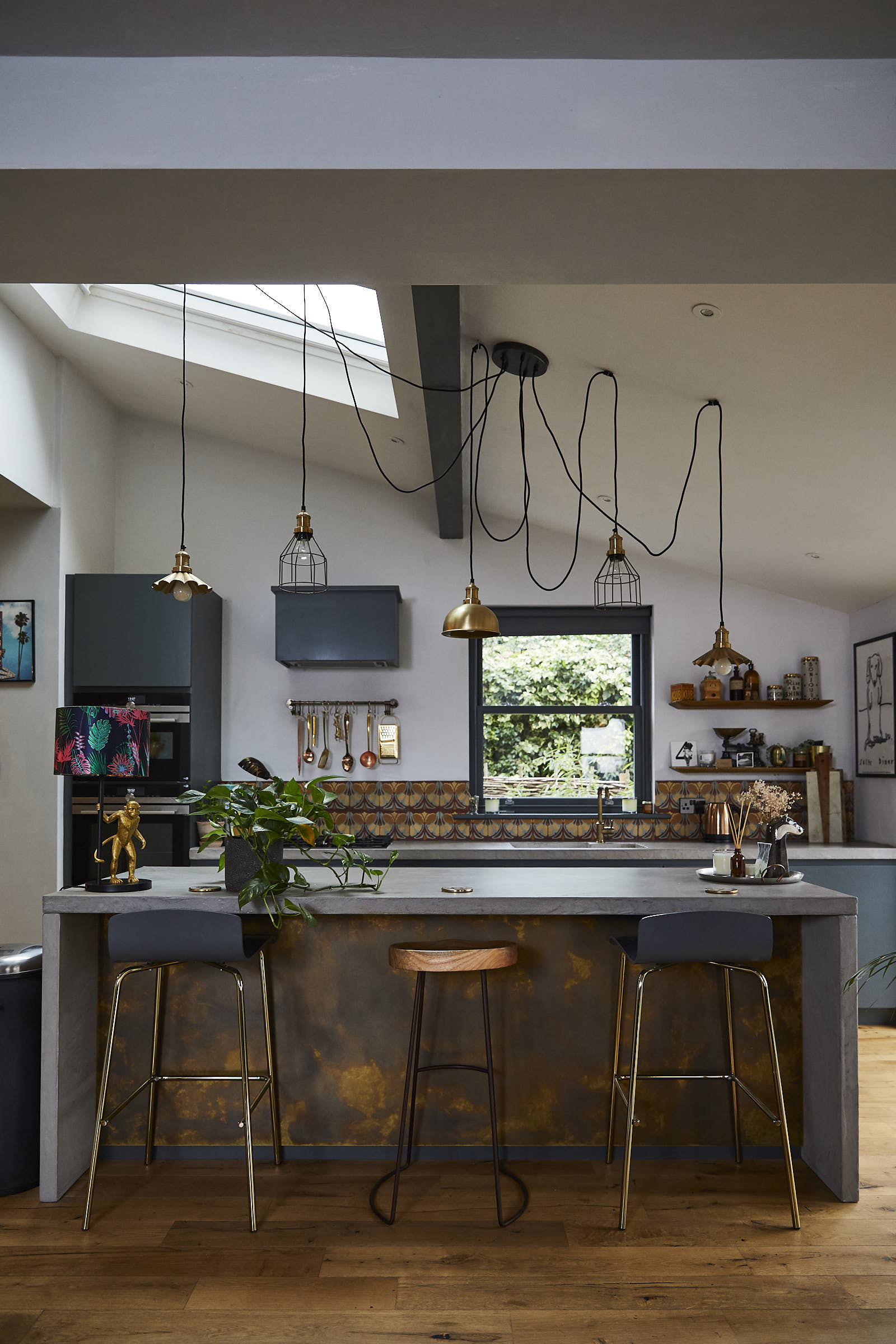 Stools under bespoke kitchen island made from concrete and brass with pendant lights hanging from above