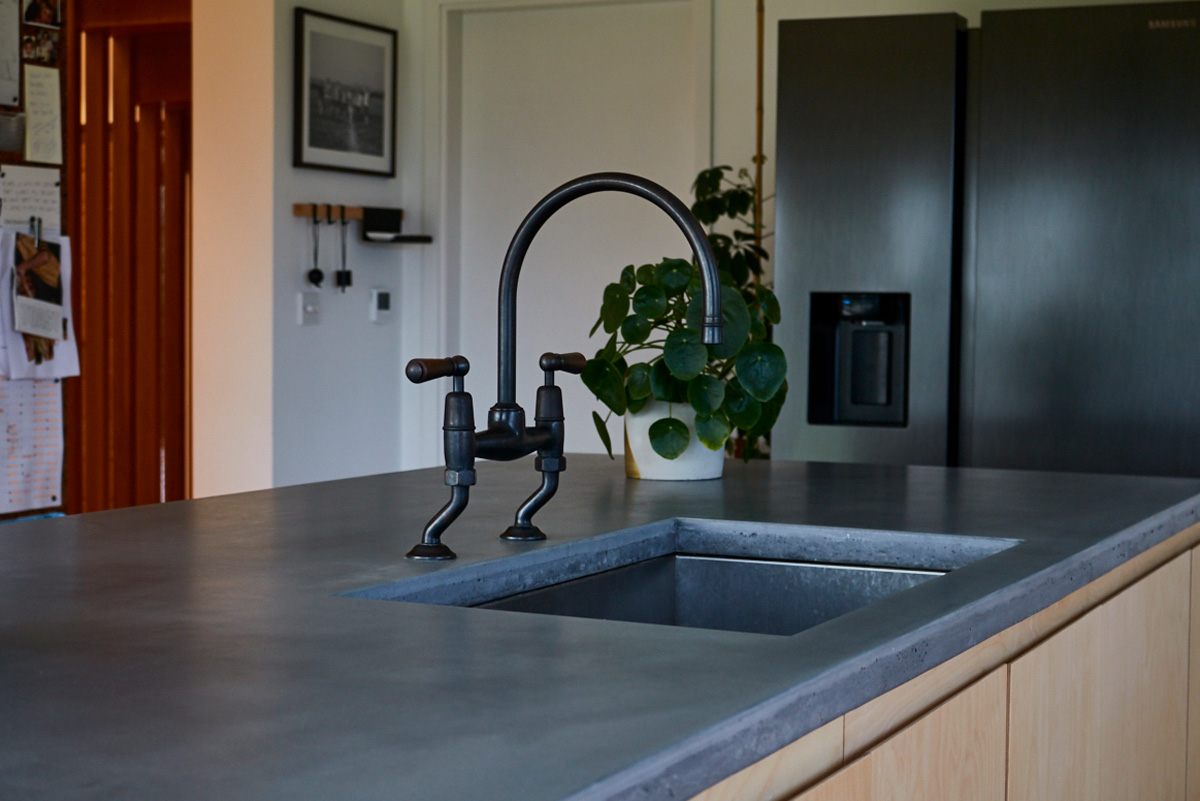 Antique transitional tap sits on solid concrete worktops