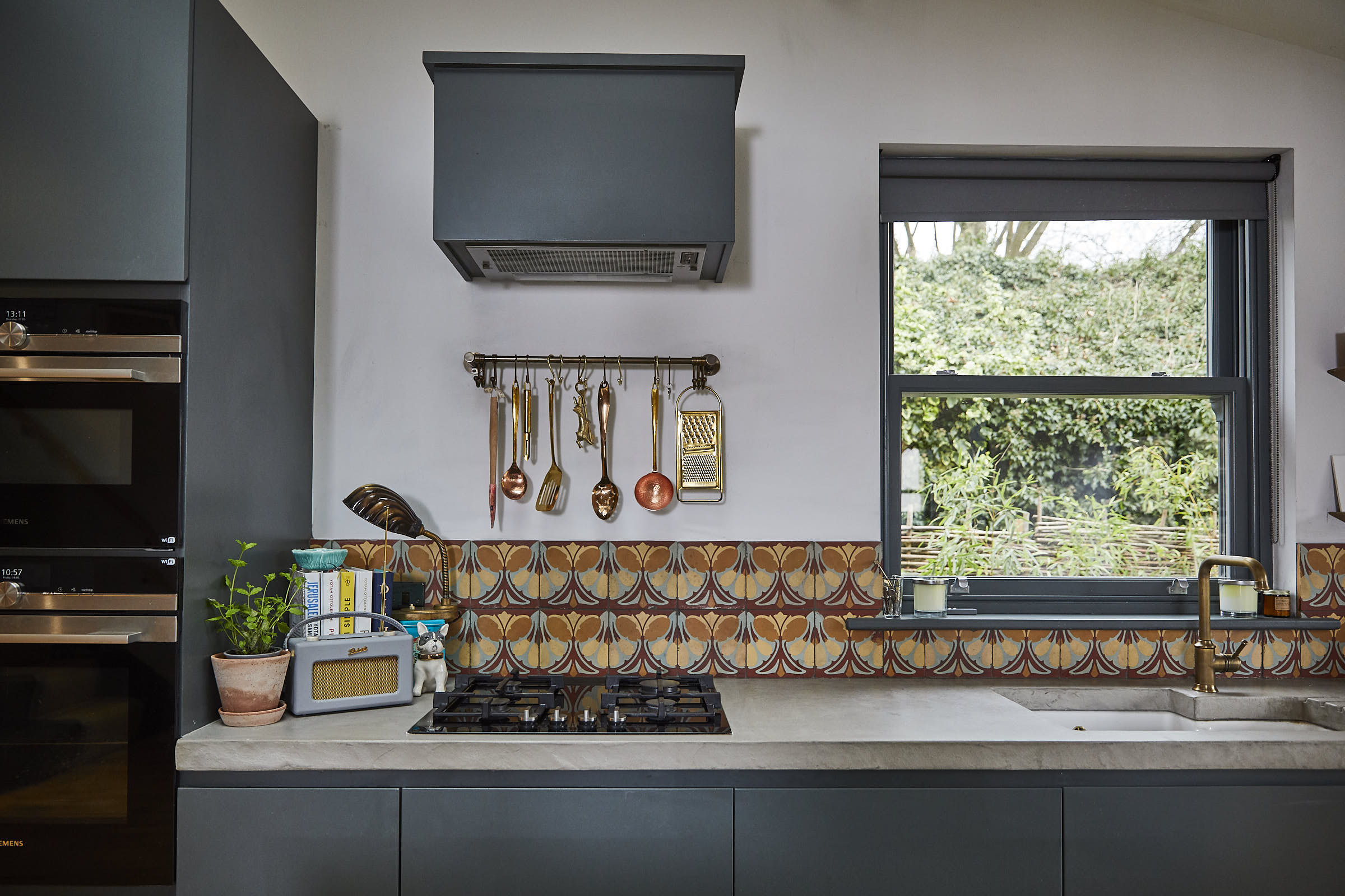Copper kitchen utensils sit under painted kitchen extractor with tiled backsplash