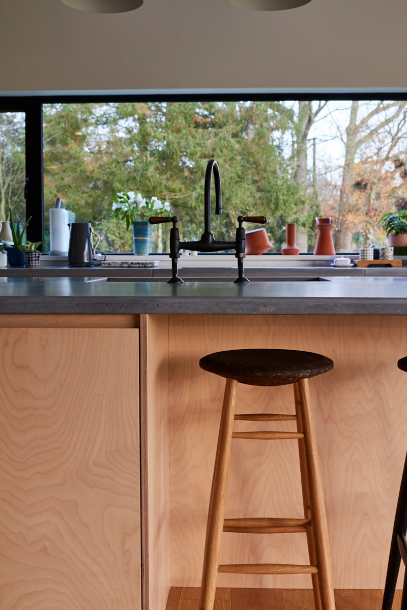 Bespoke birch plywood kitchen units and custom concrete grey worktops make island