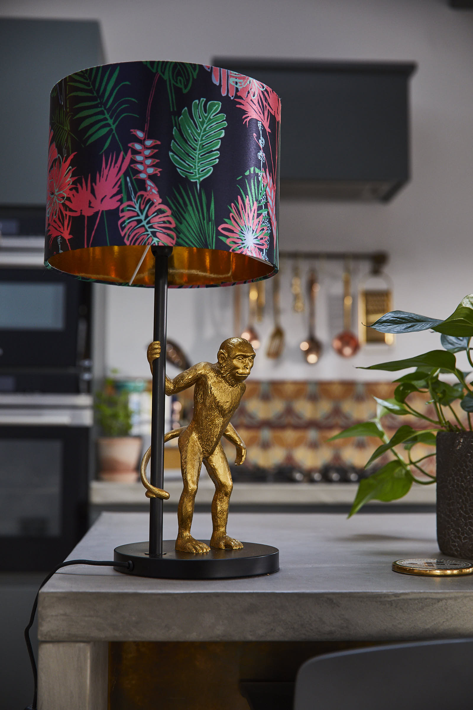 Gold monkey lamp holding colourful pink shade