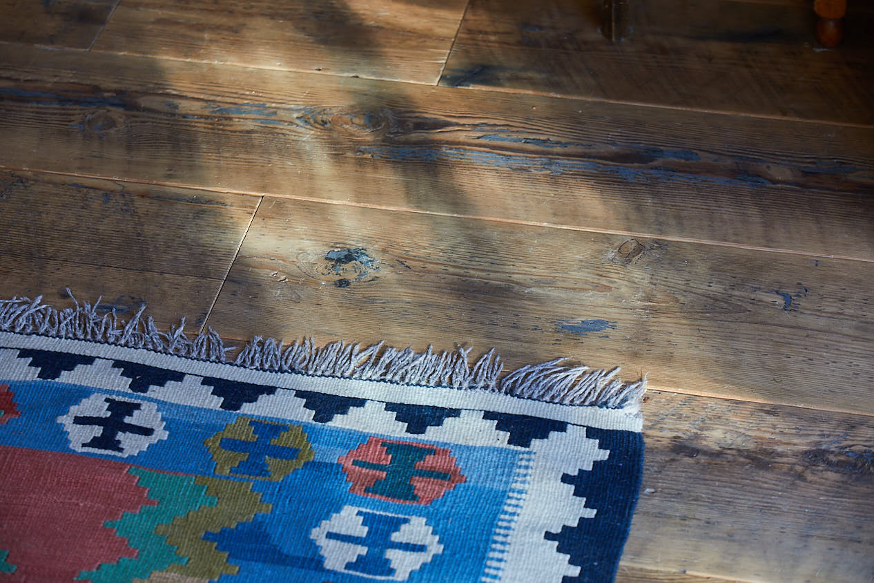 Reclaimed floor boards with Kashgai rug