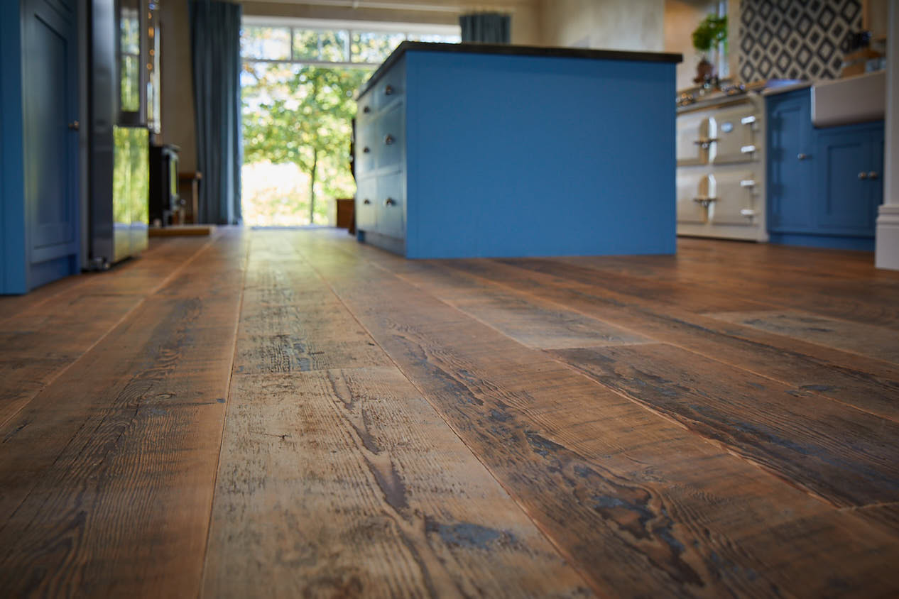 Brown rustic flooring with blue kitchen