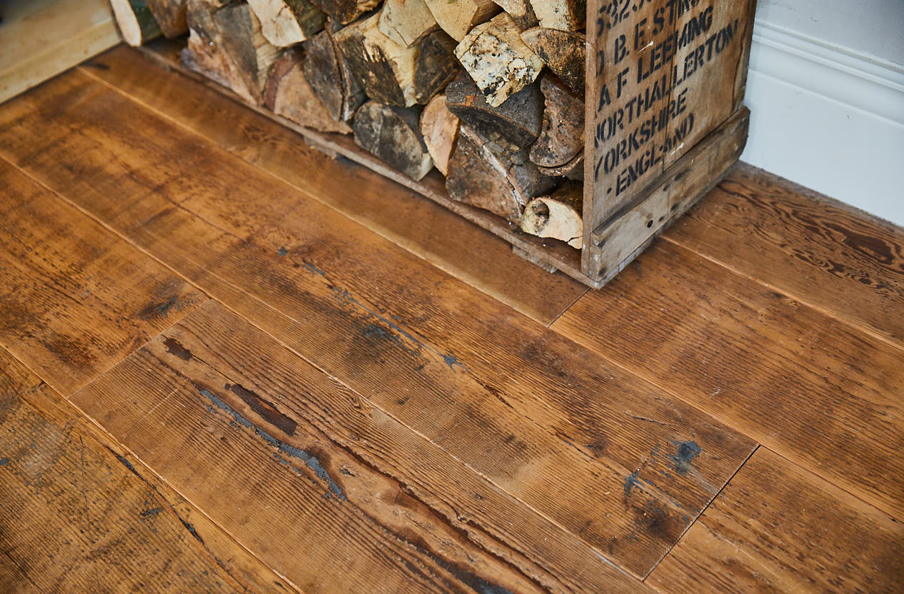 Log basket on reclaimed pine floor boards