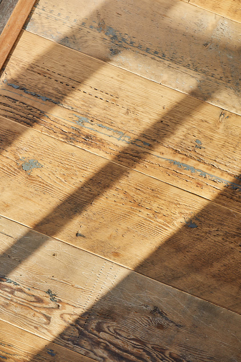 Shadows cast on raw reclaimed mill pine floor boards