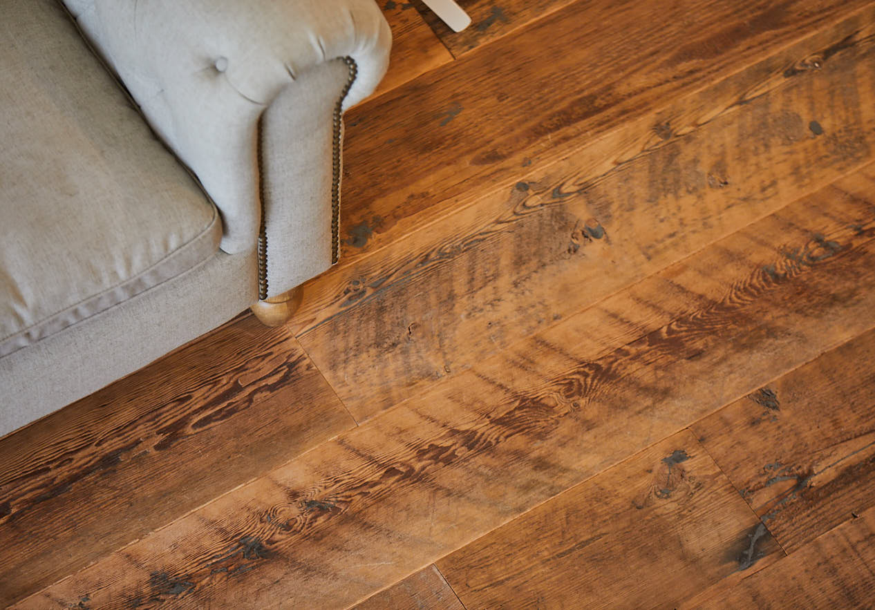 Reclaimed rustic flooring sits under upholstered sofa