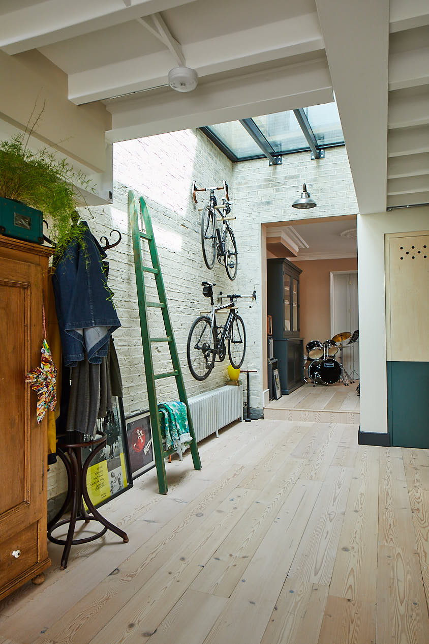 Green ladder and bikes stored against painted white wall