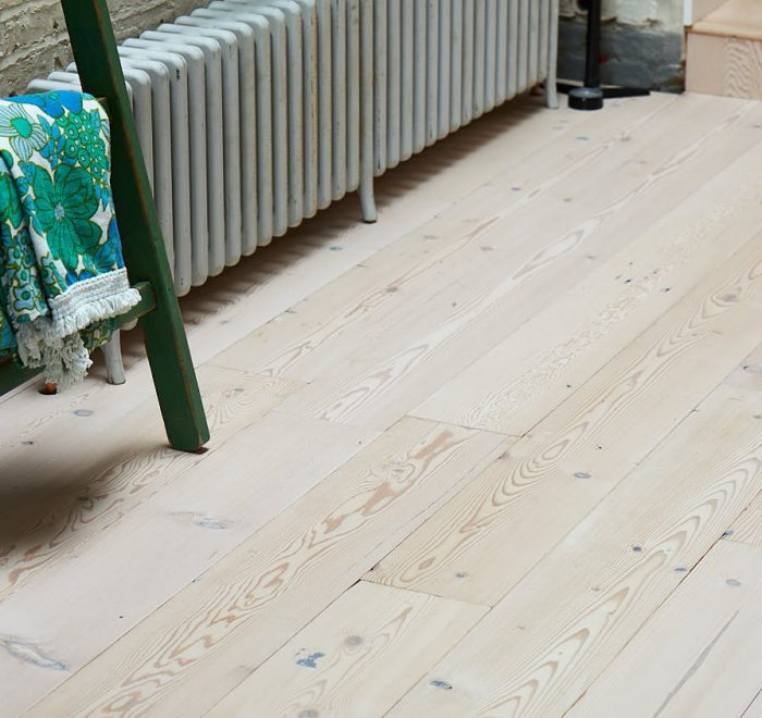 Whitewash pine flooring with green painted ladder