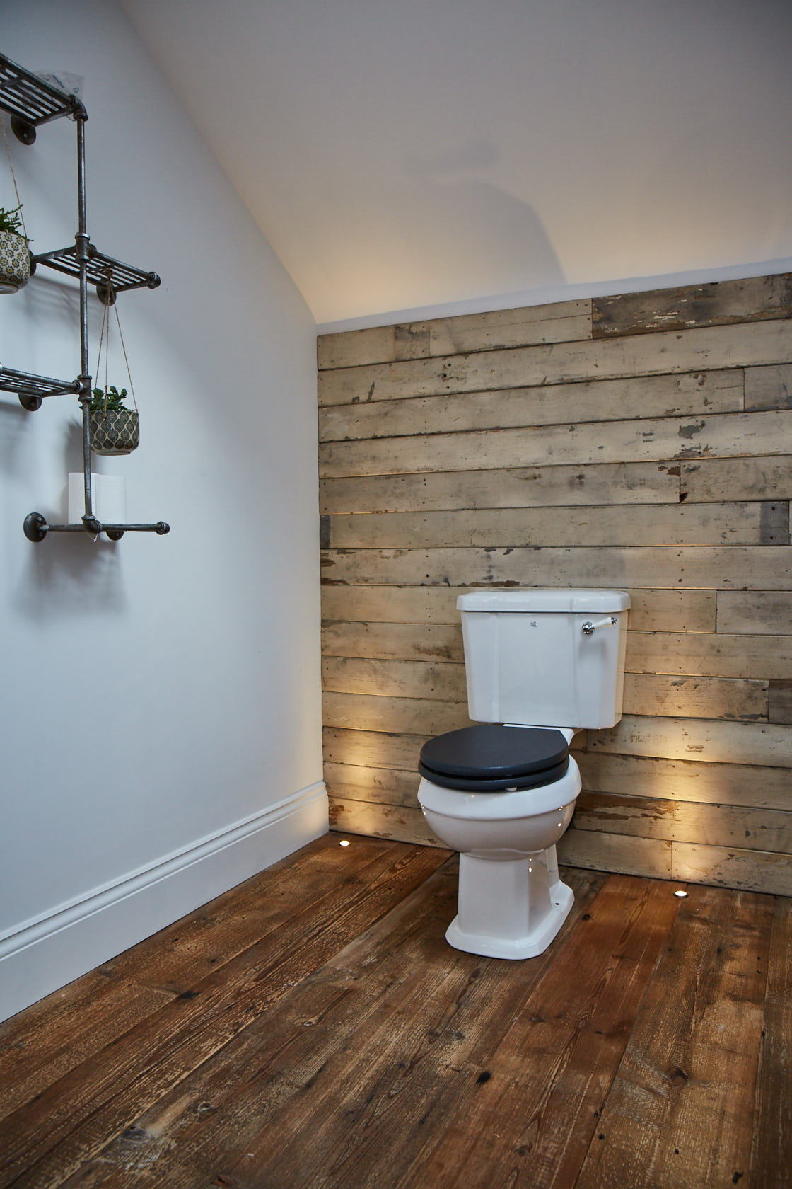 White rustic cladding behind traditional toilet