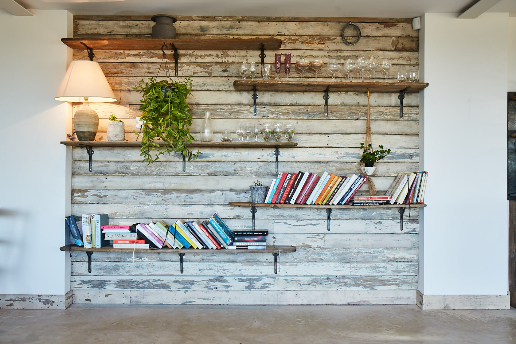 Cladded white wall with open rustic shelves on cast brackets