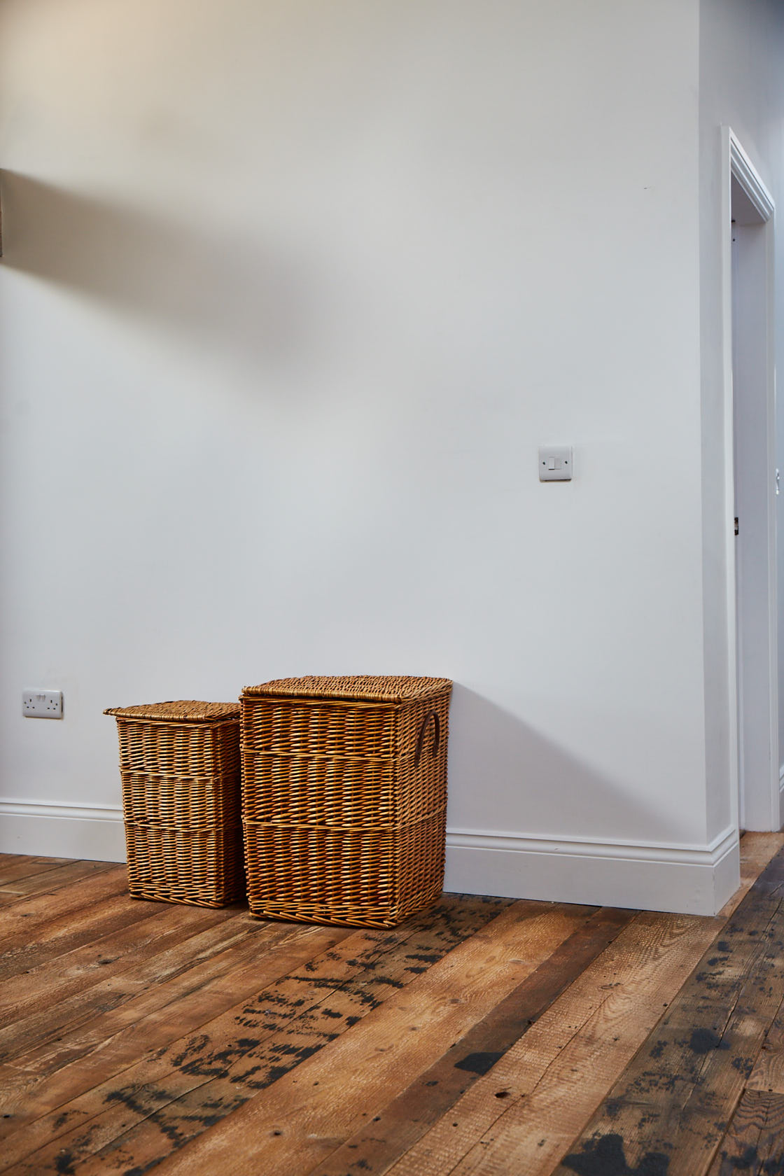 Baskets sit on reclaimed barn brown wood flooring