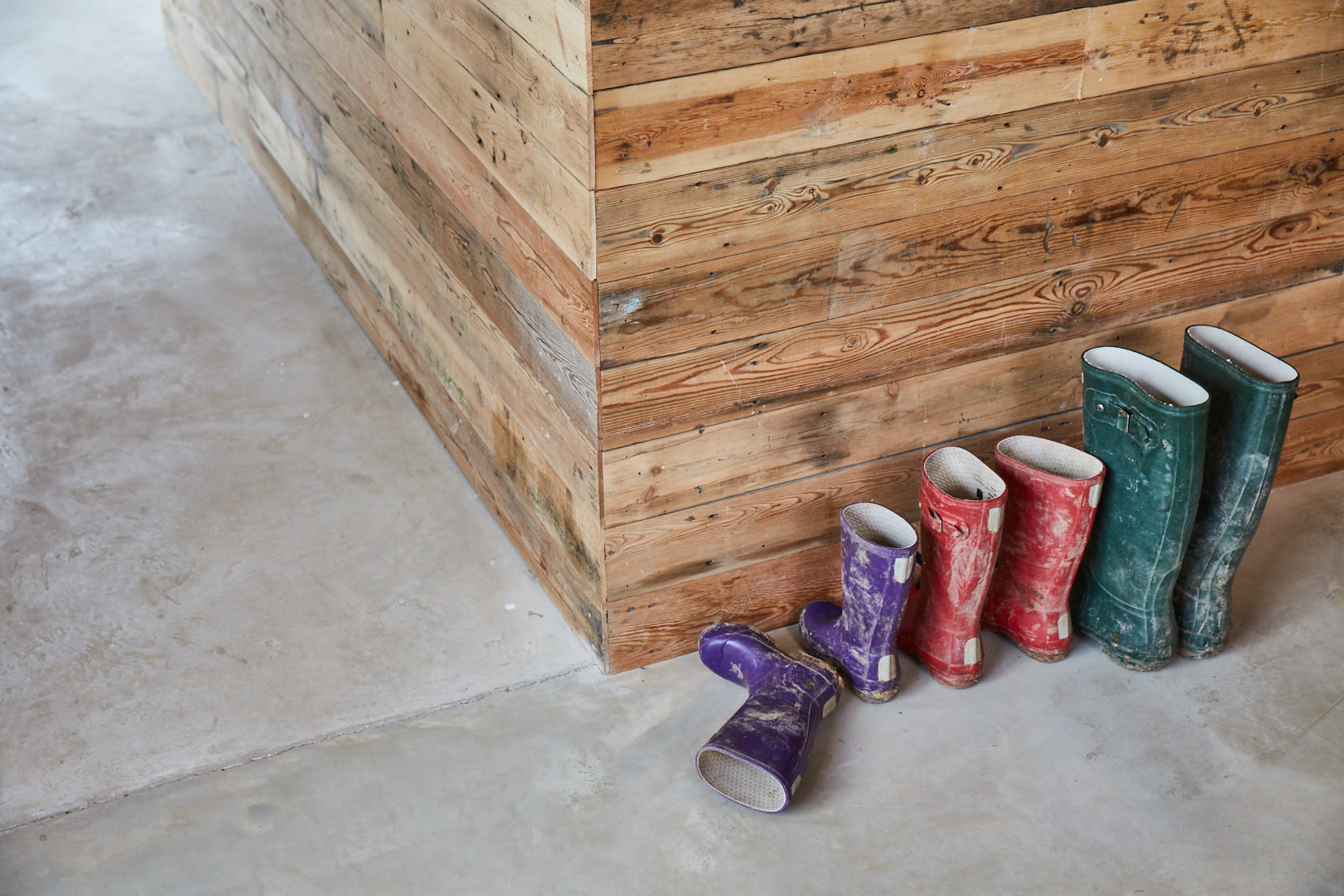 Colourful wellingtons sat on concrete floor