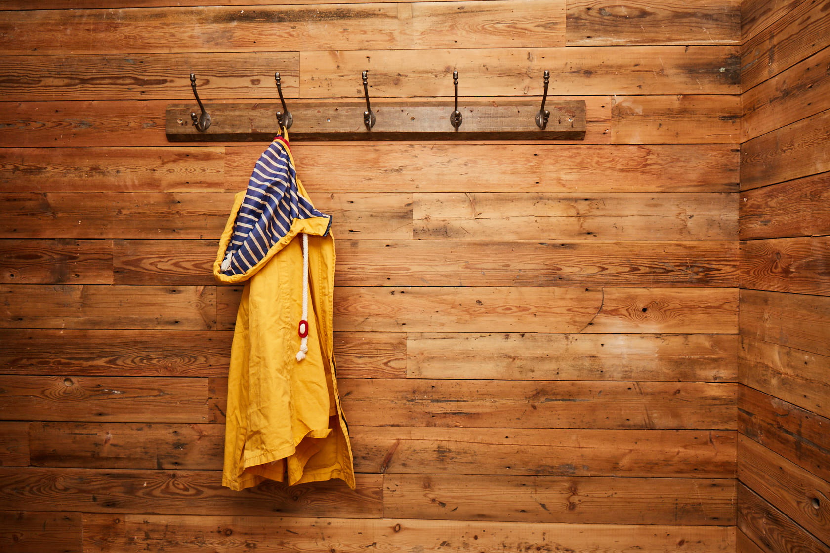 Bright yellow coat against reclaimed pine wall cladding