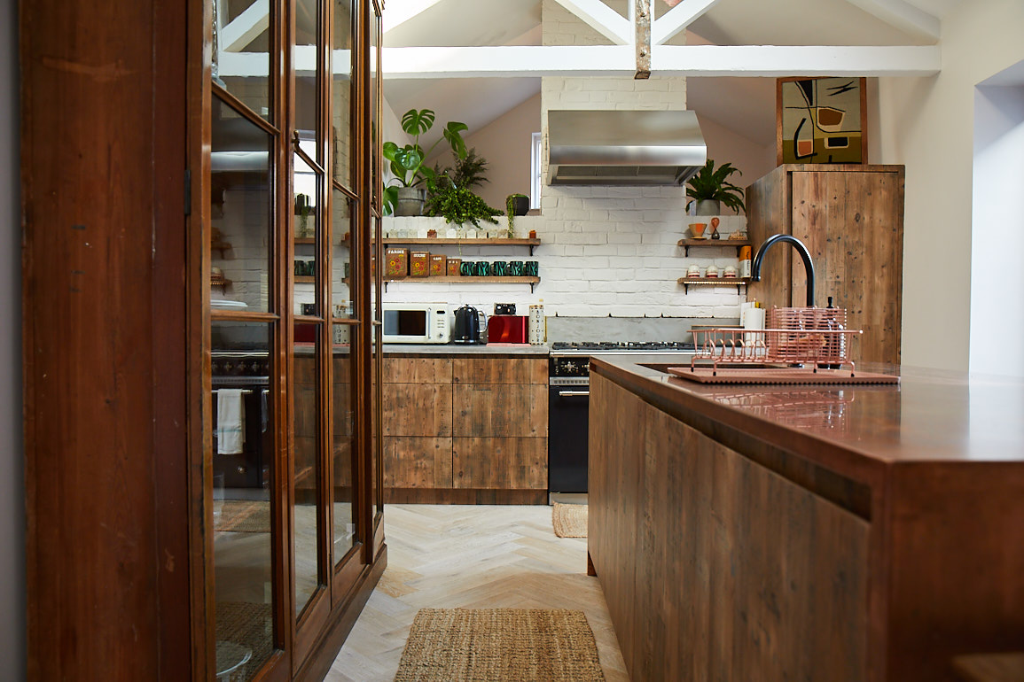 Original glass unit in open plan bespoke kitchen with copper worktops and reclaimed engineered pine units