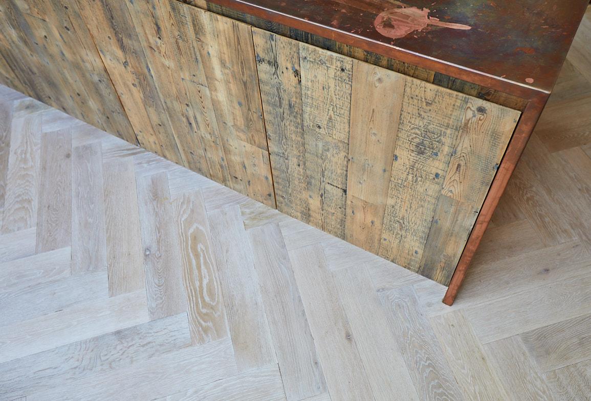 Reclaimed pine kitchen unit sit on whitewash oak parquet flooring