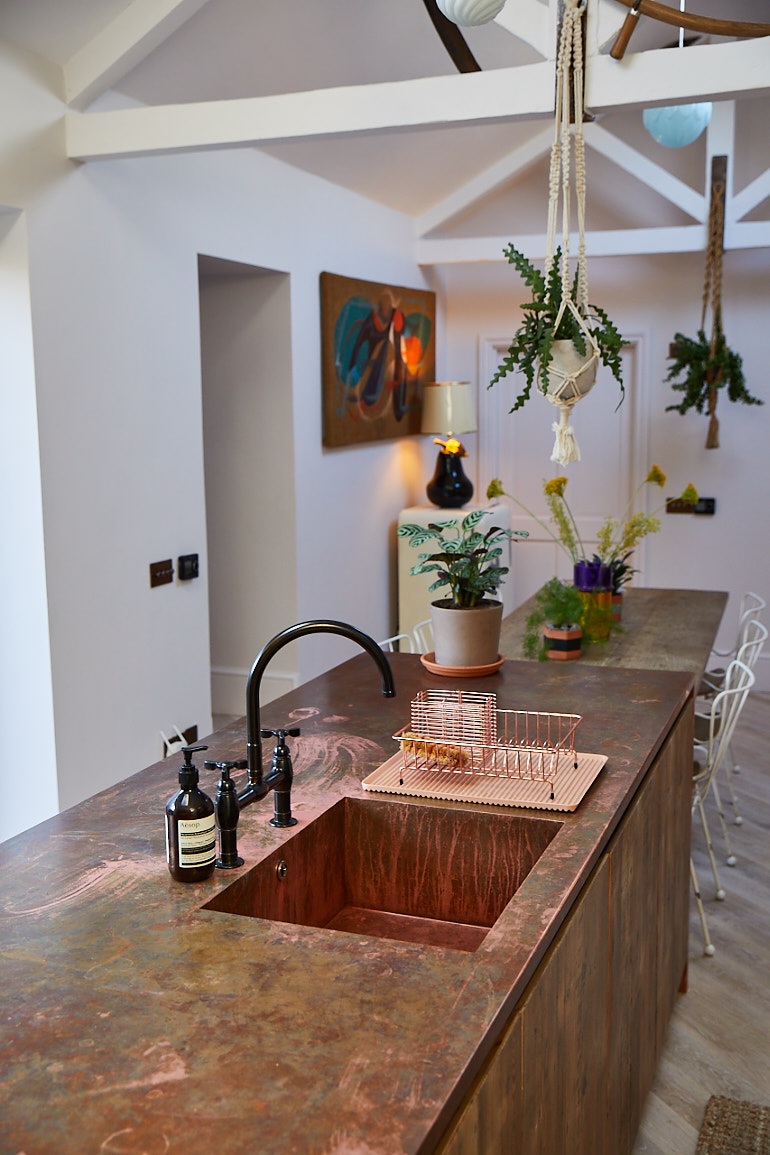 Copper worktop with seamless single sink and black mixer tap