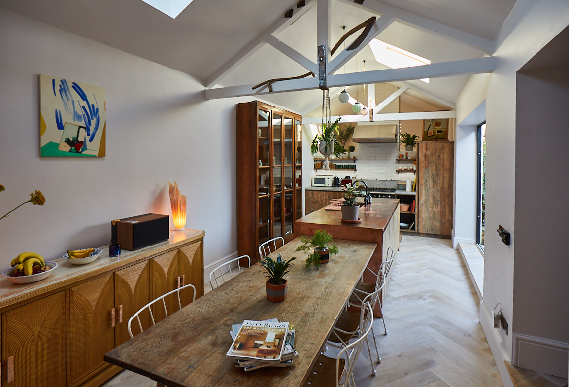 Open plan kitchen and dining with reclaimed table and bespoke copper metal island