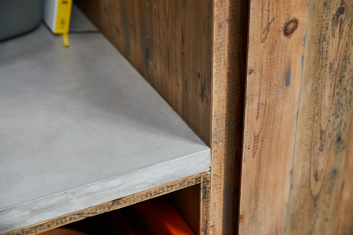 Solid concrete kitchen worktop hits in to reclaimed pine larder unit
