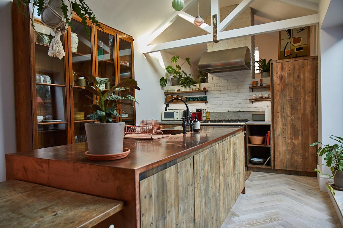 Reclaimed rustic bespoke open plan kitchen island with copper worktop and parquet oak flooring