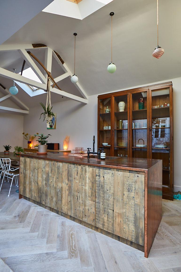Bespoke kitchen island in front of original glass cabinet