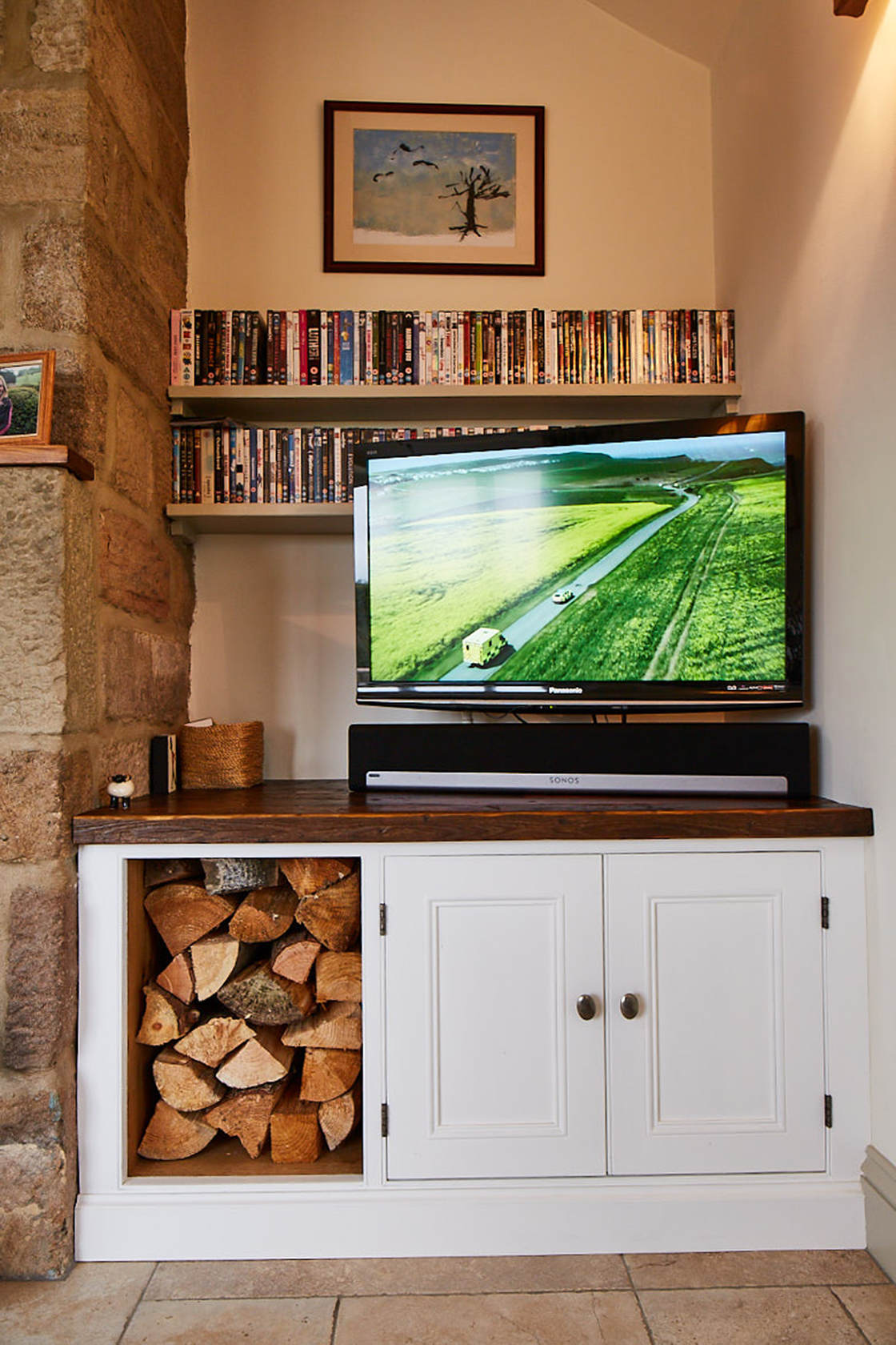Full fited tv unit with log storage fitten in to farmhouse alcove