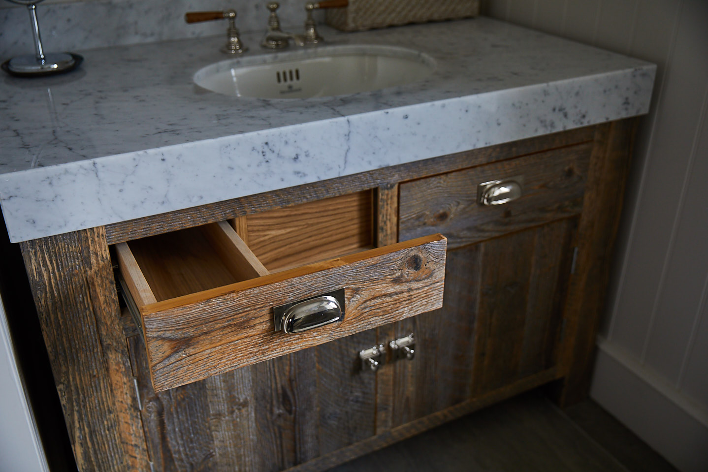Rustic vanity drawer is shaped around pipes