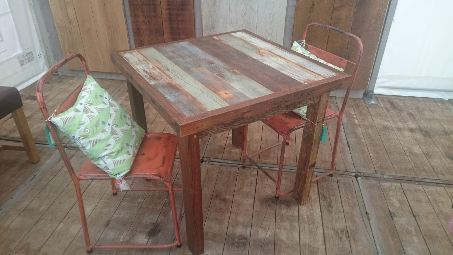 Square rustic bistro table with red metal industrial chairs