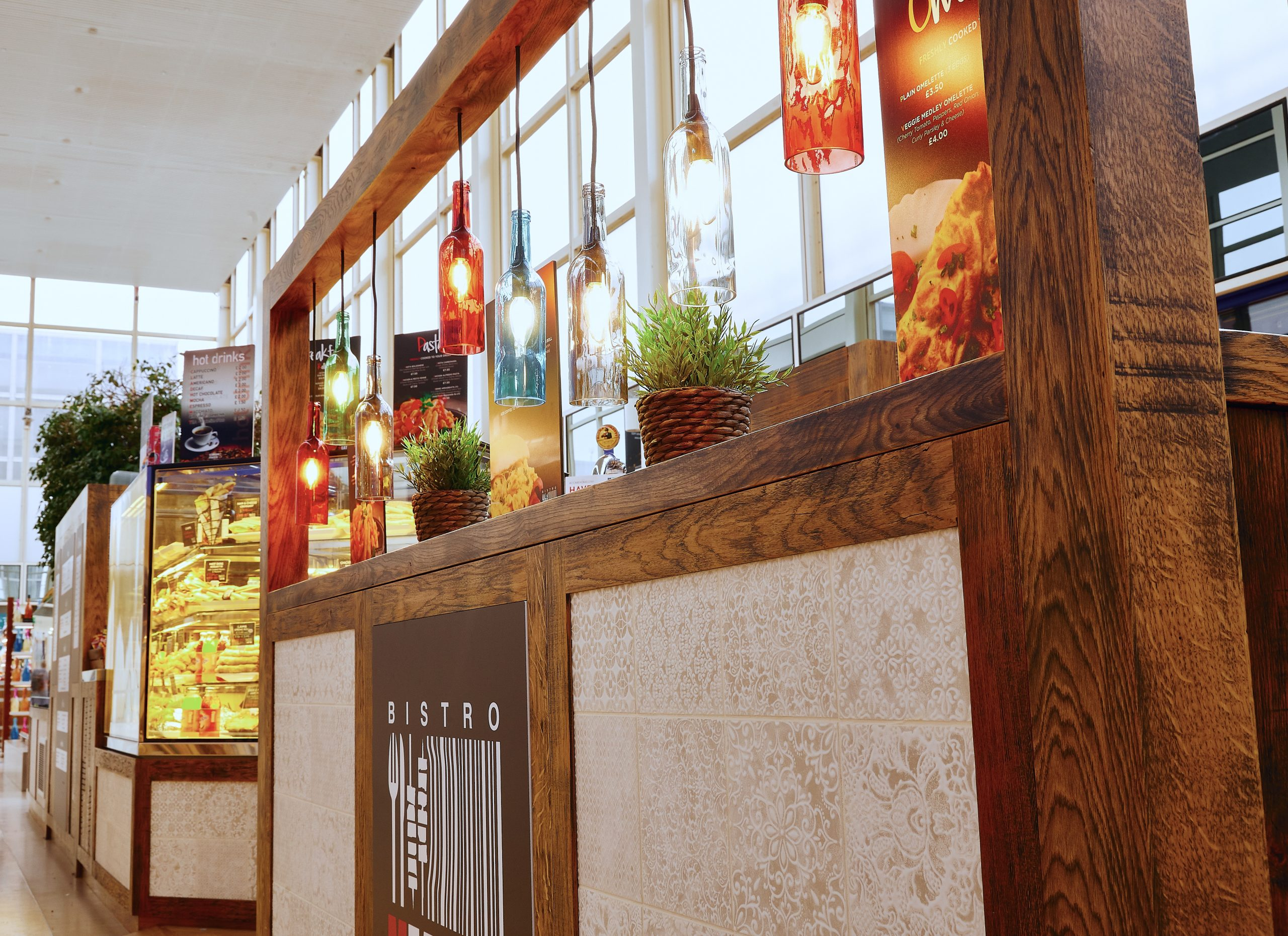 Colourful wine bottle lights hang above rustic bistro seating area