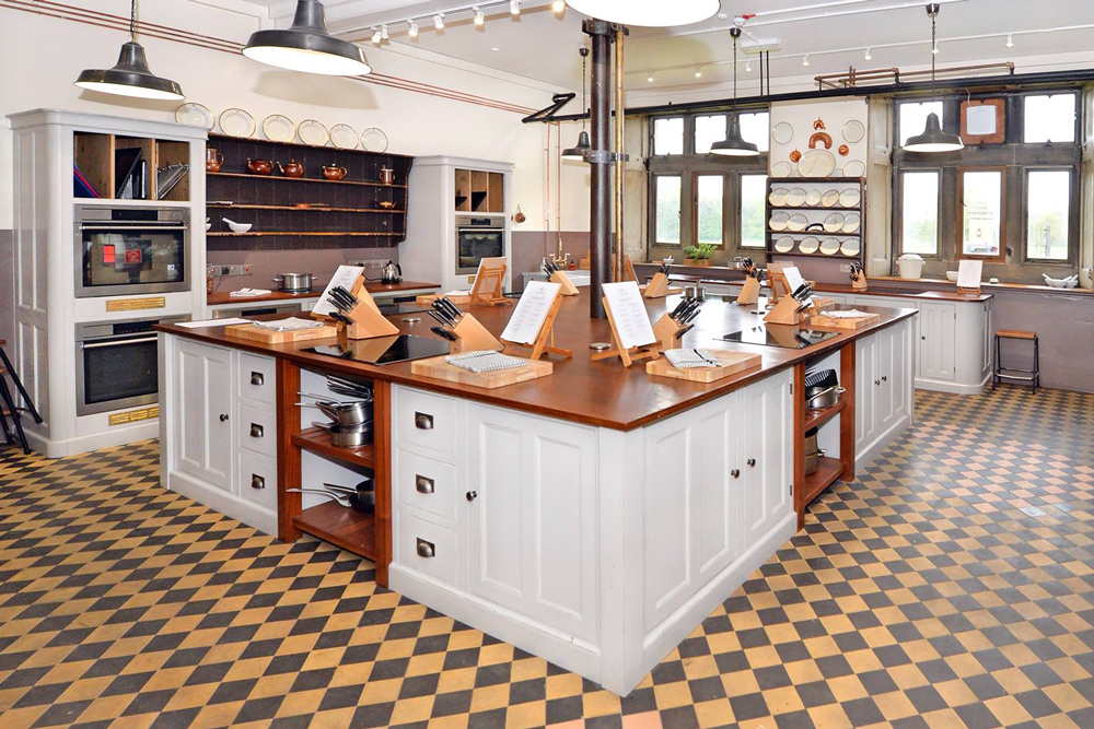 Cookery school large island with teak worktop set up ready for class to begin