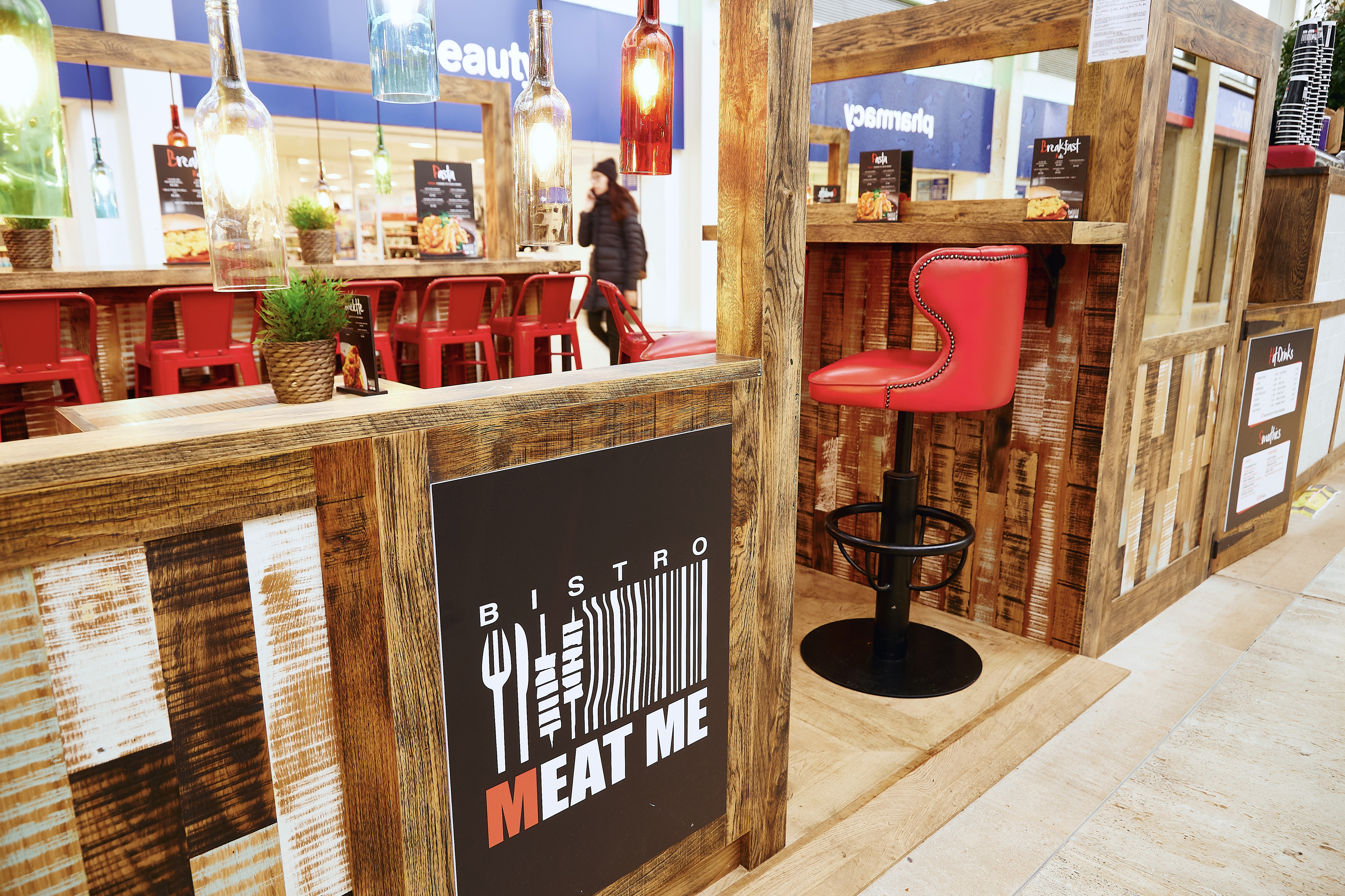 Meat Me Bistro branding with rustic wood surround and red leather bar stool