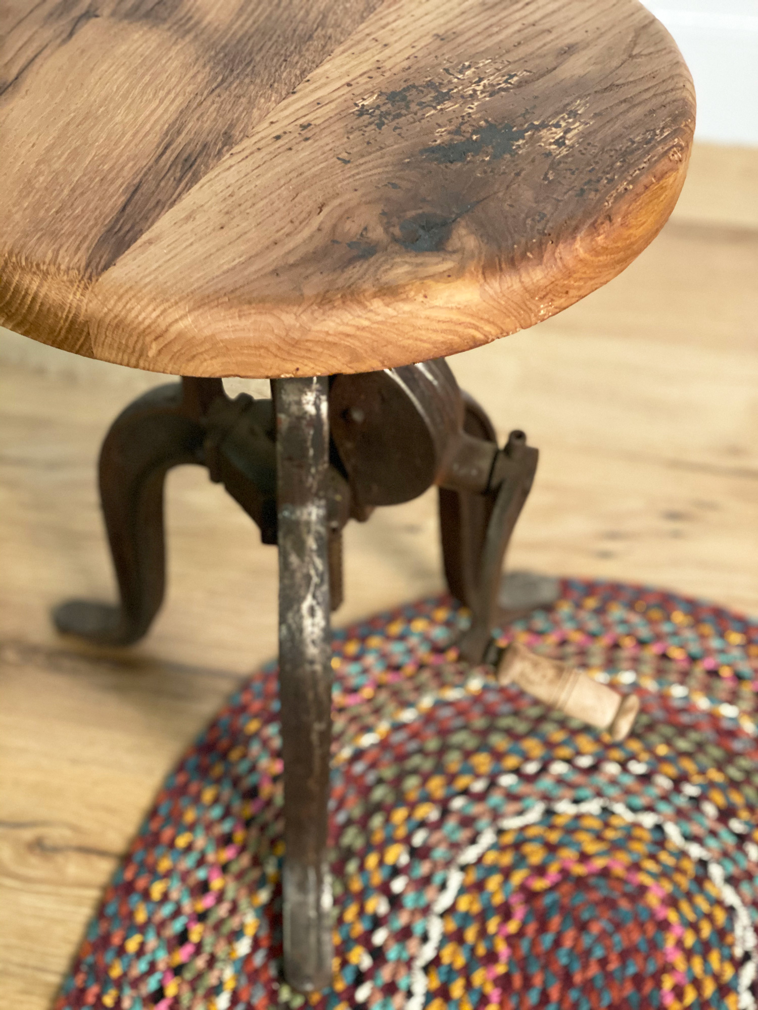Oak side table with cast iron base or red rug