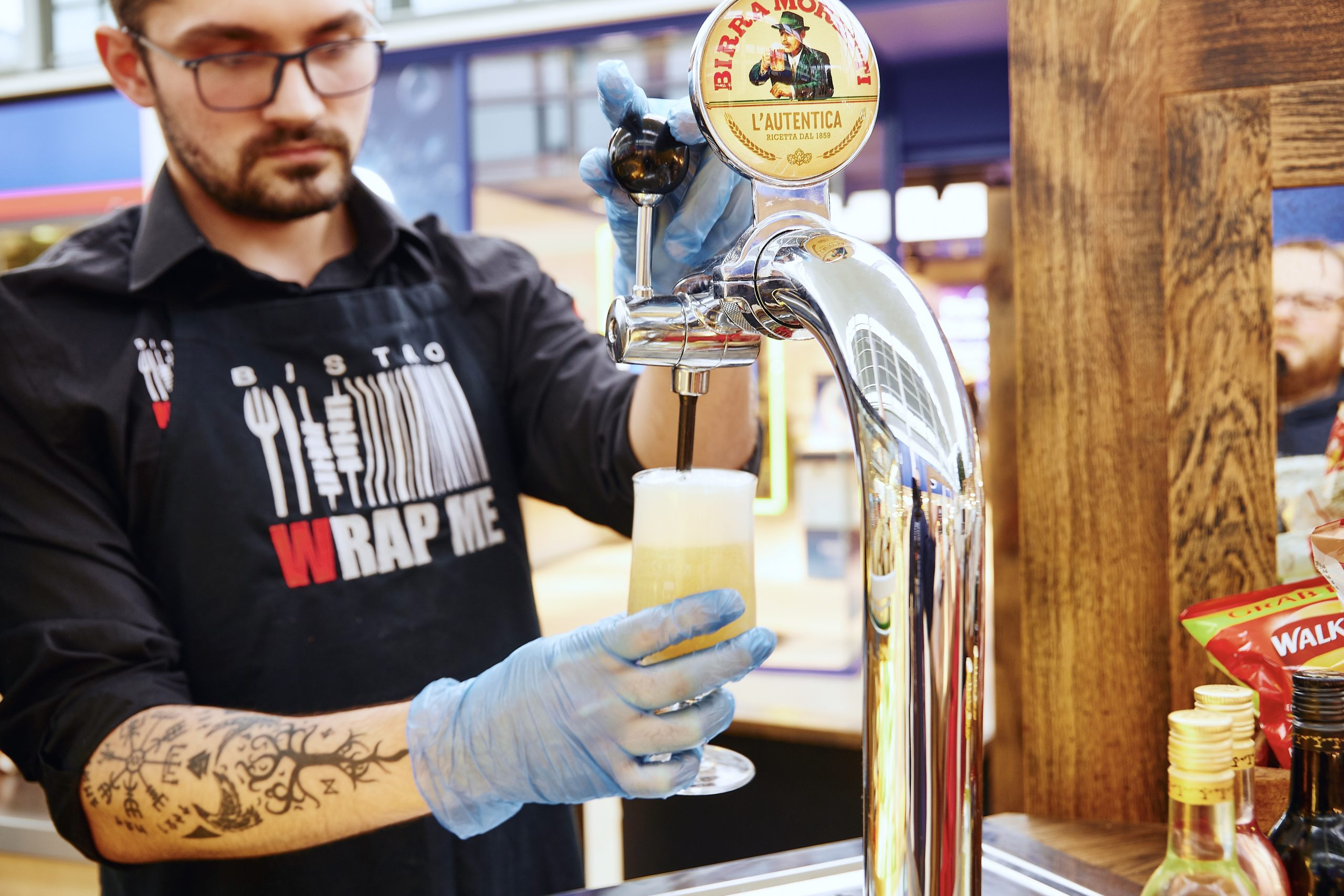 Bistro worker pours half pint of moretti