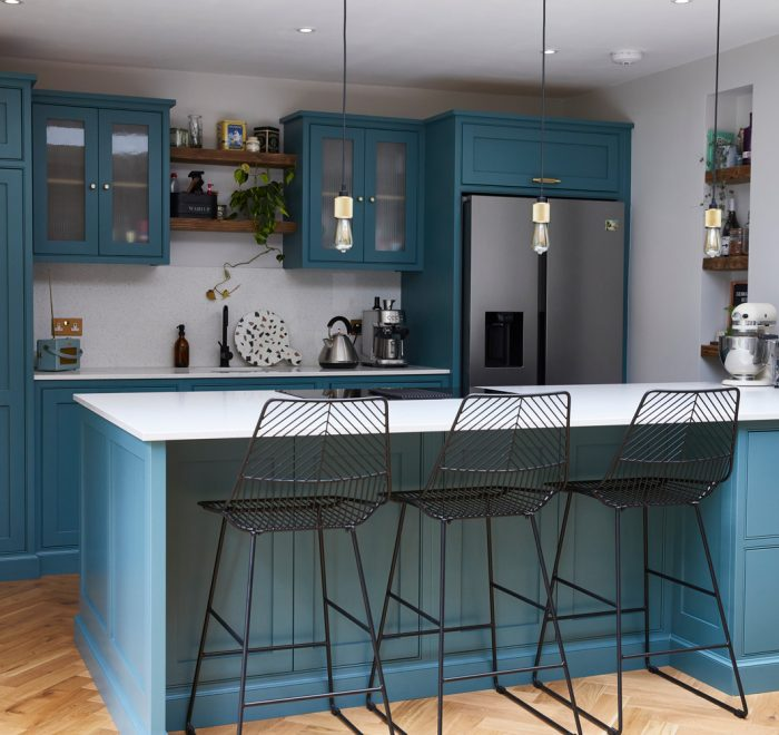 Bespoke blue green kitchen with black metal bar stools finished with brass buster + punch hardware