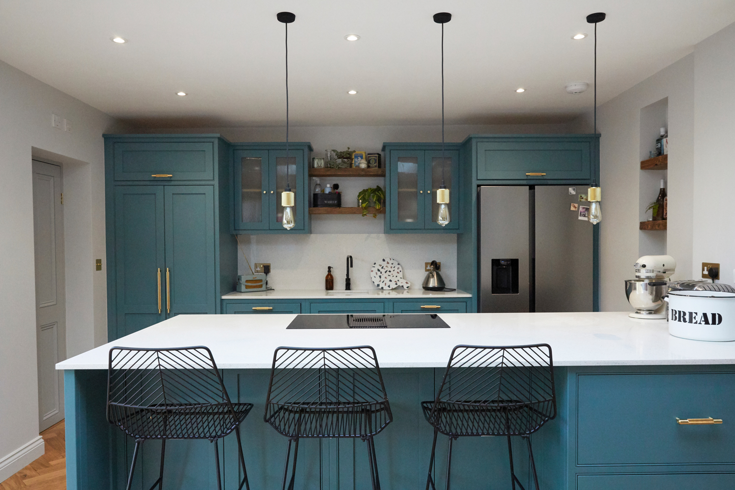 Bespoke kitchen peninsular with black metal barstools and buster + Punch brass bar handles