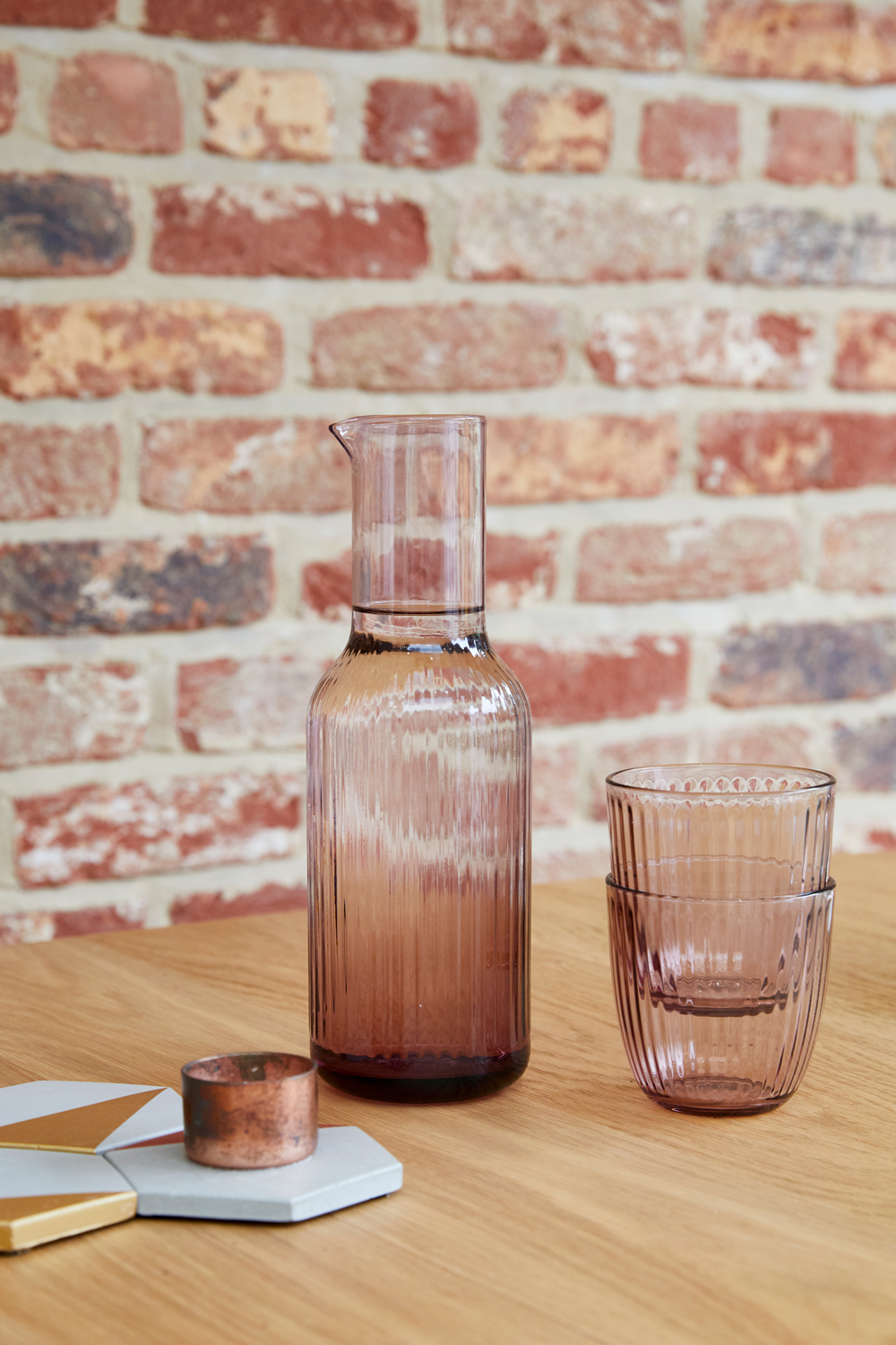 Pink glasses sit on oak dining table with exposed brick backdrop