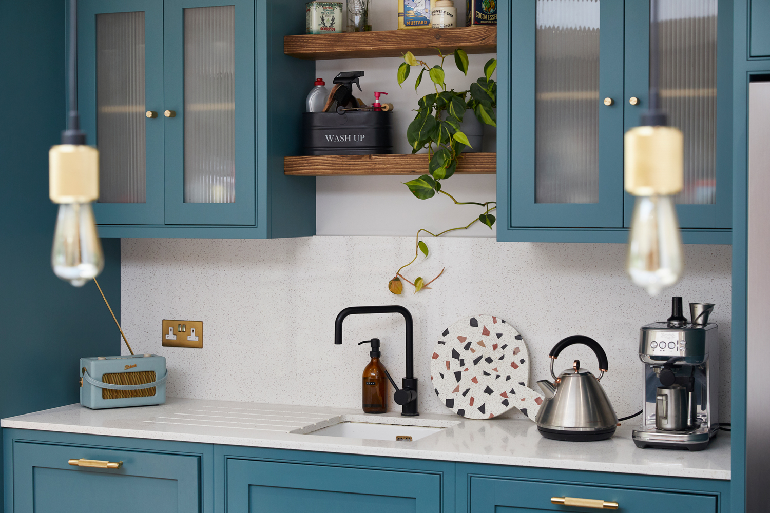 Reclaimed rustic pine scaffold board shelves sit above sink unit with quartz worktop