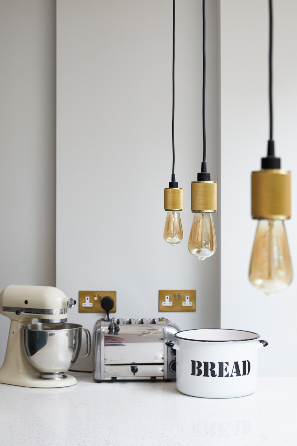Toaster, Mixer and Bread post sit on white quartz worktop with heavy metal brass pendants by Buster and Punch hang above
