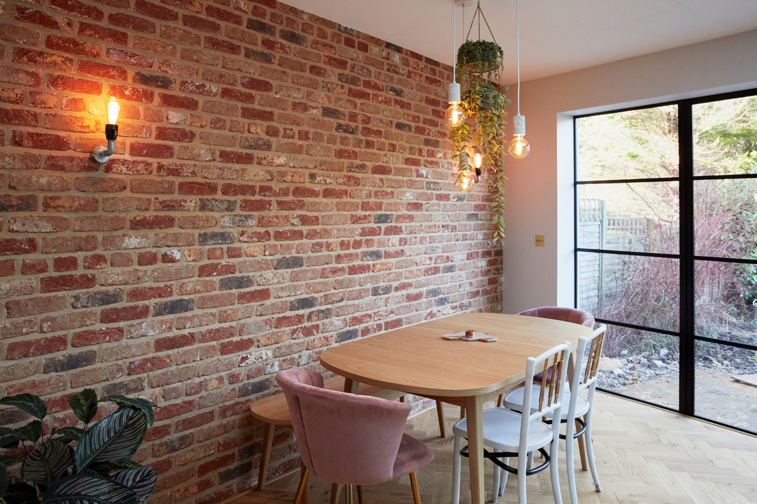 Exposed brick wall with clean oak dining table and upholstered chairs