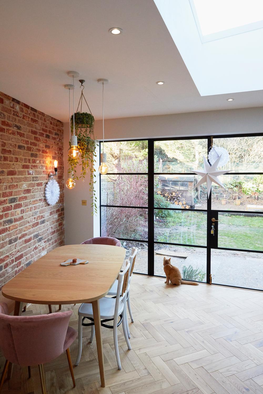 Oak modern kitchen table sits on oak parquet flooring