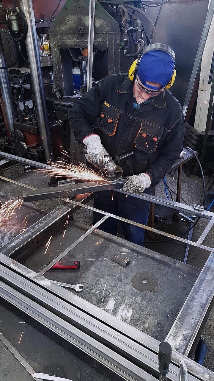 Welder sanding bespoke metal doors