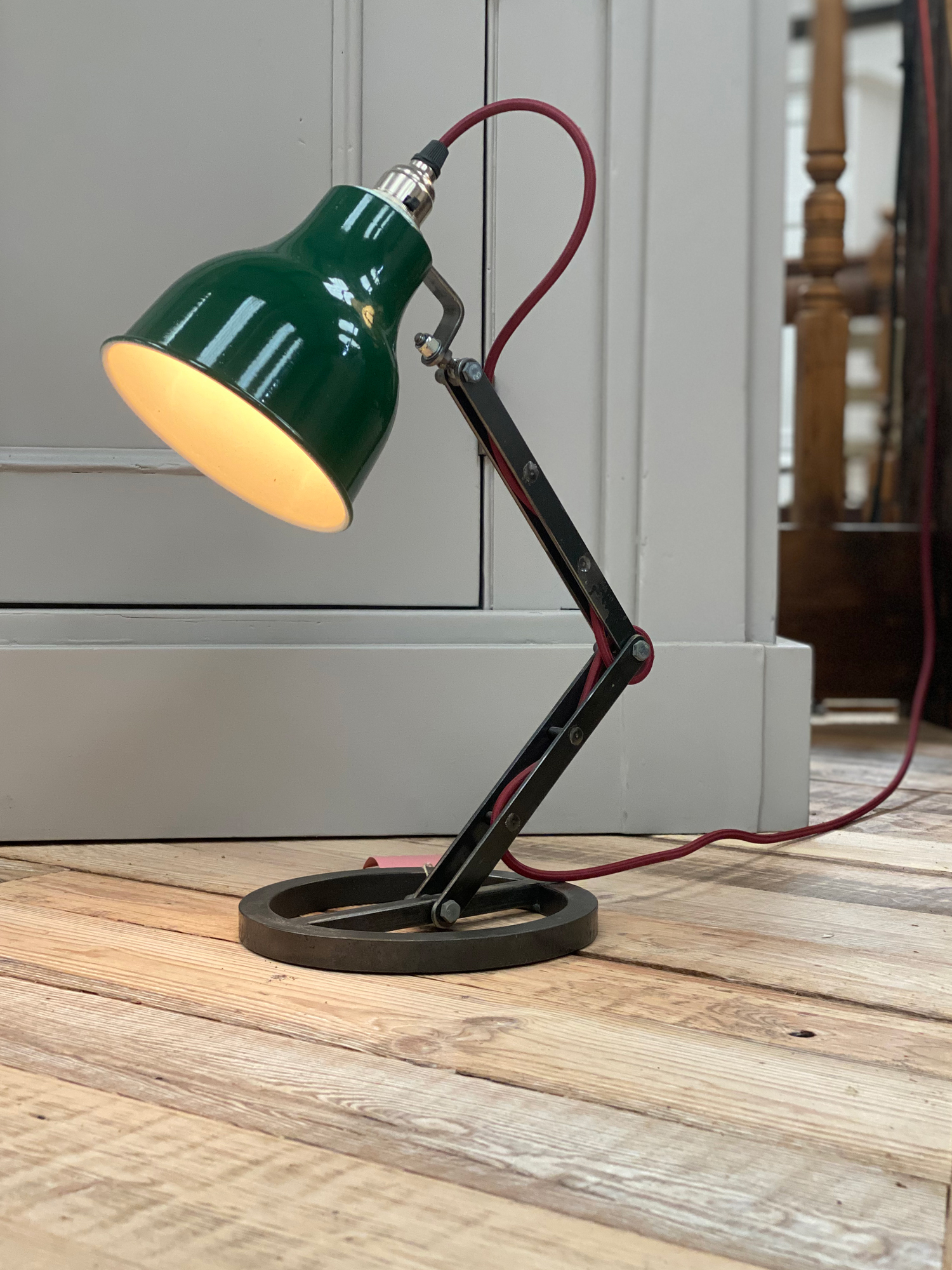 Industrial table lamp with green shade and red textile cord